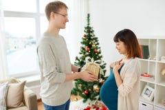 给圣诞节礼物的丈夫怀孕的妻子 免版税库存图片