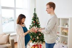 给圣诞节礼物的丈夫怀孕的妻子 库存照片