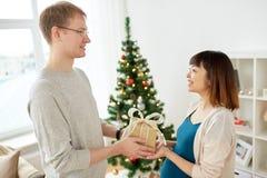 给圣诞节礼物的丈夫怀孕的妻子 库存图片