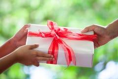 给圣诞节礼物的父母的手儿童女孩 免版税库存照片