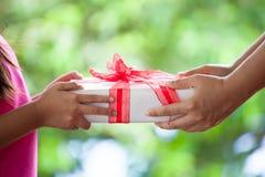 给圣诞节礼物的父母的手儿童女孩 图库摄影