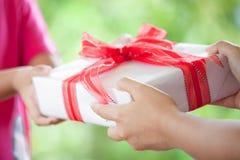 给圣诞节礼物的父母的手儿童女孩 库存图片