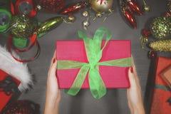 给在桌上的妇女一件箱子礼物 免版税库存照片