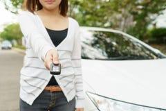给在汽车字体的少妇一辆关键汽车在街道上的 免版税库存图片