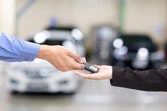 给在汽车字体的年轻女商人一辆关键汽车  免版税库存图片