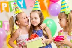 给在生日聚会的俏丽的孩子礼物 免版税库存图片