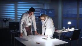 给在问候的白色外套的两位电子工程师手见面对他们的工作讲话
