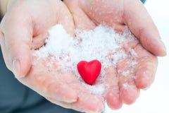 给在雪的手心脏,华伦泰` s天,捐赠题材  免版税库存图片