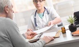 给处方的女性医生她的患者 库存图片