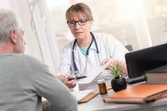 给处方的女性医生她的患者 免版税图库摄影