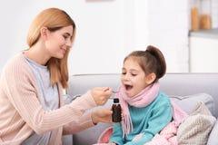给女儿咳嗽syru的母亲 免版税库存照片