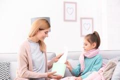 给女儿在沙发的母亲纸组织 免版税库存照片
