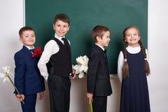 给女孩的男孩在空白的黑板背景附近开花,小学孩子,穿戴在经典黑衣服,小组学生,编辑 图库摄影