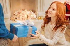给她的儿子圣诞节礼物的爱恋的母亲 免版税库存照片