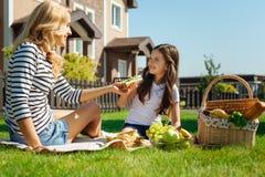 给她的女儿在野餐的有同情心的母亲一个三明治 库存图片