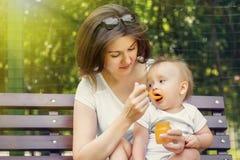 给她的婴儿孩子补全哺养的南瓜纯汁浓汤的母亲在室外的好日子 妈妈和孩子坐长凳在公园 免版税库存图片