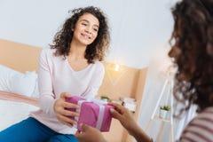 给她的最好的朋友礼物的美丽的女孩 免版税库存图片