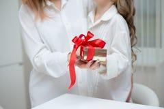 给她的母亲圣诞节礼物的女儿 库存图片