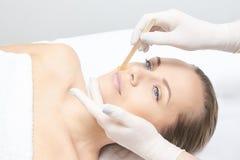 给妇女腿打蜡 糖头发撤除 激光服务epilation 沙龙蜡美容师做法 免版税库存图片