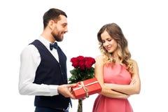 给妇女花和礼物的愉快的人 免版税库存图片