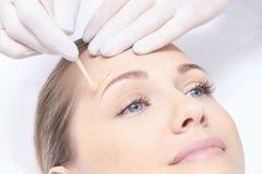 给妇女身体打蜡 糖头发撤除 激光服务epilation 沙龙蜡美容师做法 免版税库存图片