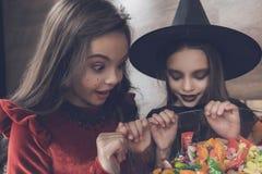 给孩子被带来的母亲在妖怪衣服穿戴了一个花瓶用糖果和甜点 免版税库存图片