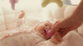 给安慰者轻便小床的挑剔婴孩 免版税库存照片