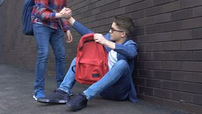 给帮手的亲切的少年学生被胁迫的书呆子男孩,支援朋友 股票视频