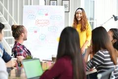 给快乐的介绍的年轻亚裔女实业家 免版税库存图片