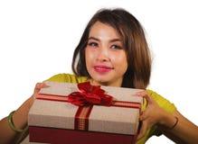 给或接受圣诞礼物或有红色的年轻愉快和美丽的亚裔印度尼西亚妇女画象生日礼物箱子 库存图片