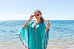 给手在海滩的愉快的少妇标志赞许 库存照片