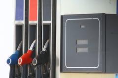 给手枪在燃料驻地和燃料表的气泵喷管加油 免版税库存图片