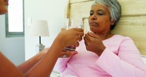 给杯水的女性医生在床4k上的病的资深妇女 股票录像