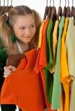 给查找机架的好奇女孩穿衣 免版税库存照片