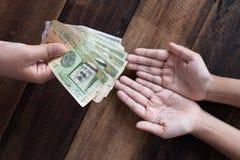 给沙特里亚尔钞票的手 免版税库存图片