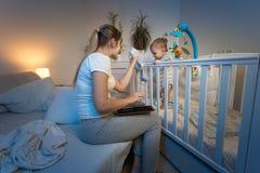 给玩具的美好的年轻母亲阅读书aand她的站立在轻便小床的小儿子在晚上 免版税图库摄影