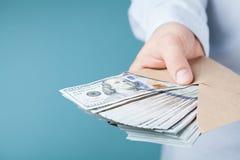 给现金金钱的商人 贷款,财务,薪金,贿款和捐赠概念 库存图片