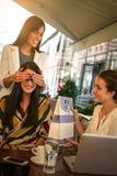 给生日礼物的女性朋友 女孩使他们的朋友惊奇 免版税图库摄影