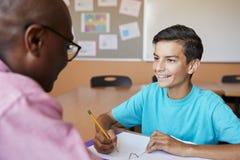 给男学生一到一学费的高中家庭教师在书桌 免版税库存图片