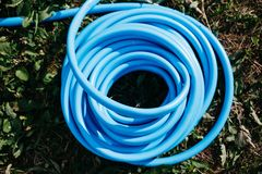给的草喝水扭转的蓝色水管在草坪顶视图 免版税图库摄影