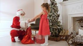 给礼物一个相当小女孩和拥抱她的圣诞老人 库存图片