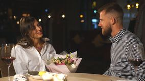 给礼物和花的英俊的年轻人咖啡馆的美丽的妇女 股票录像