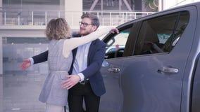 给礼物汽车,慷慨的男性做意外对于有闭上的眼睛的心爱的女性并且情感地给汽车和她 股票录像