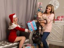 给礼物的圣诞节女孩小婴孩 作为克劳斯加工好的圣诞老人妇女 免版税库存照片