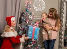 给礼物的圣诞节女孩小婴孩 作为克劳斯加工好的圣诞老人妇女 免版税库存图片