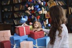 给礼物的小美丽的俏丽的女孩她愉快的怀孕的母亲-户内 免版税库存图片
