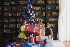 给礼物的小美丽的俏丽的女孩她愉快的怀孕的母亲-户内 免版税图库摄影