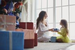 给礼物的小美丽的俏丽的女孩她愉快的怀孕的母亲-户内 图库摄影