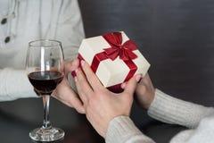 给礼物的白色衬衫的年轻帅哥他的女朋友,当吃浪漫晚餐时 免版税库存照片