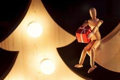 给礼物盒的木玩具坐与减速火箭的圣诞树 免版税库存照片